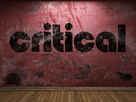 critical: critical word on red wall Stock Photo