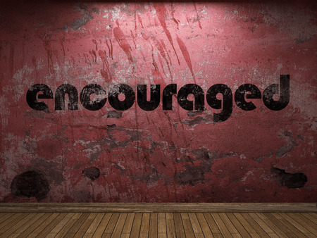 encouraged: encouraged word on red wall Stock Photo