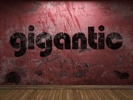 gigantic: gigantic word on red wall Stock Photo
