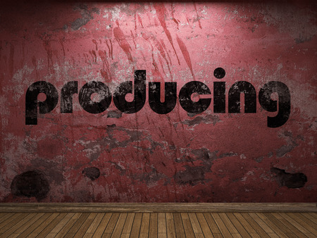 producing: producing word on red wall Stock Photo