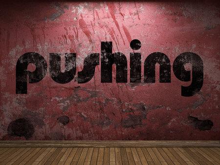 empujando: empujando la palabra en la pared roja Foto de archivo