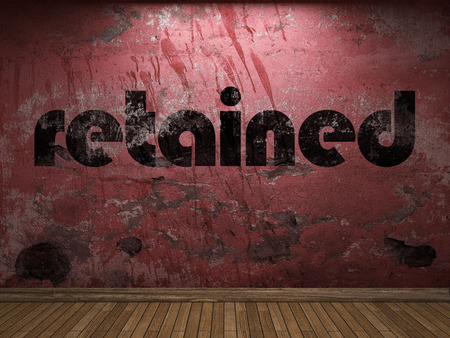 retained: palabra retenido en la pared roja Foto de archivo