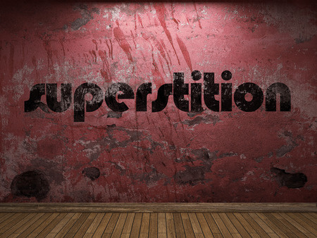 superstition: superstition word on red wall Stock Photo