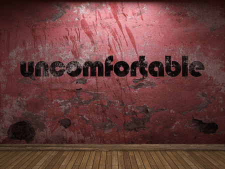 uncomfortable: uncomfortable word on red wall Stock Photo