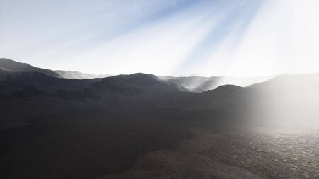 the sun's rays against the backdrop of the mountains and the lava-rocky wet shore in the foreground