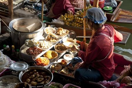 RATCHABURI, THAILAND - December 11: A merchant prepares hot noodle ready to be served on the boat at floating market, Ratchaburi. This is the most traditional and famous floating market in thailand.