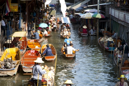 RATCHABURI, THAILAND - December 11: Many merchants row along the canal to sell their goods at floating market. This is the most traditional and famous floating market in thailand.