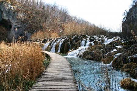 A wooden pathway to waterfall in Plivice Lake, Croatia photo