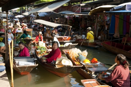 RATCHABURI,THAILAND -DEC 11  Merchants row along the canal to sell their goods at floating market on Dec 11, 2011 in Ratchaburi  This is the most traditional and famous floating market in Thailand  Editorial