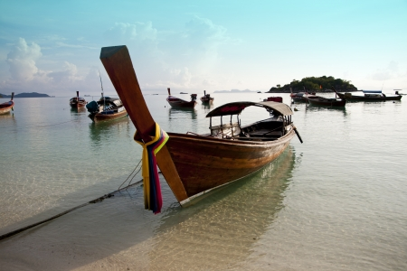 Traditional wooden boat in clear water, Lipe island, Thailand photo