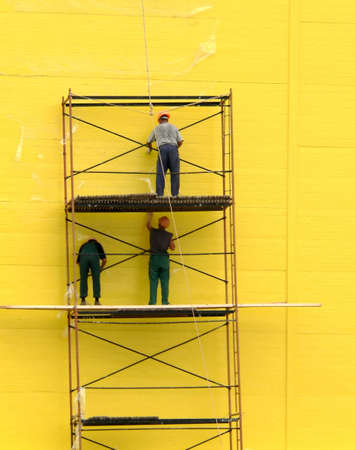 Three workers on background of yellow wall Stock Photo