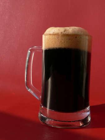 schwarzbier: Krug dunkles Bier auf rotem Hintergrund