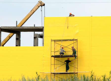 Workers on scallolding on yellow wall background Stock Photo