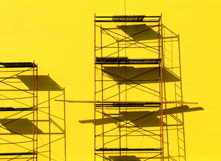 colouration: Constructions scaffolding on the yellow wall background Stock Photo