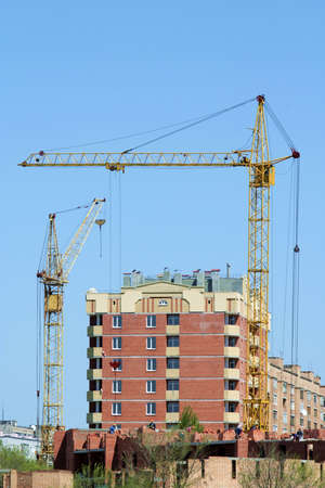 Two lifting cranes on building of the new house.