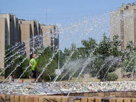 torrid: Fountain. Hot summer. Boy under the sprays of the water.