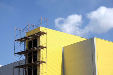 erector: Yellow building and scaffolding. Sky with clouds.