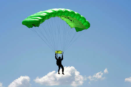 Parachuter  with green parachute on sky background  photo