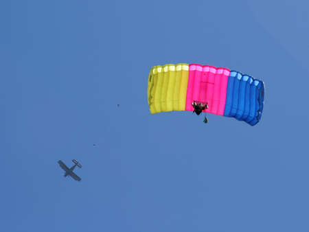 Parachuter with colored parachute on sky background 2 photo
