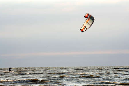 high winds: Surfer with kite on the sea waves 2