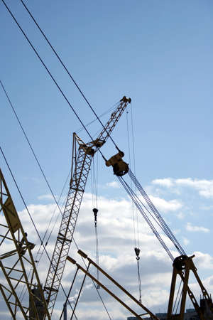 erect: Construction. Silhouettes of the cranes on the sky background. Stock Photo