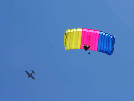 Parachute jumper and airplane on blue sky background  photo