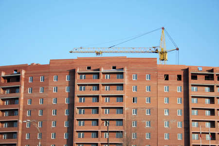 erect: Lifting crane on building of the new house on sky background Stock Photo