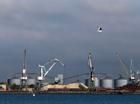 seaports: Big cranes and oil tanks in the seaport. Loading work in seaports