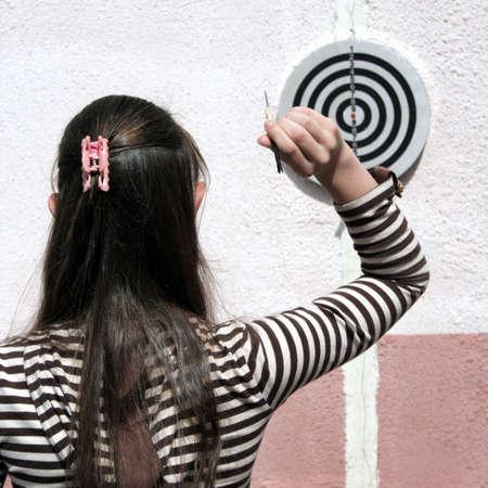 fling: Girl throws dart to target Stock Photo
