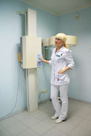 roentgenograph: young woman, doctor-radiologist connects the equipment for take of x-ray picture