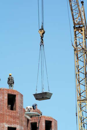 raises: lifting-crane to raise a bricks on the top floor of a under construction building
