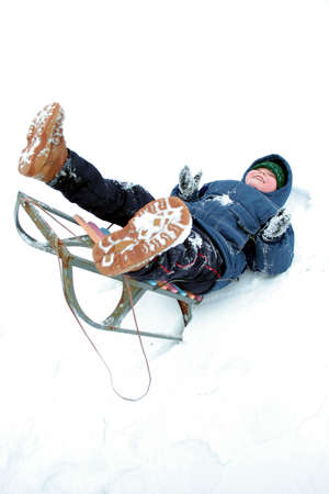 Falling to the snow. Winters riding of the boy. Stock Photo