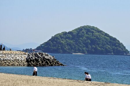 A student walking on a sandy beach and a small island off the coast