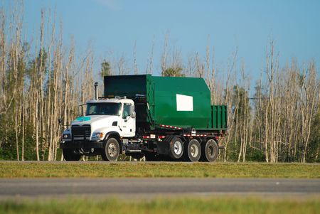 Green dump truck on the road