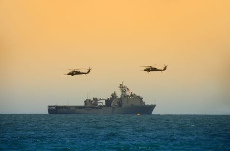 a battleship: Navy battleship cruising to mission with helicopter escorts Stock Photo
