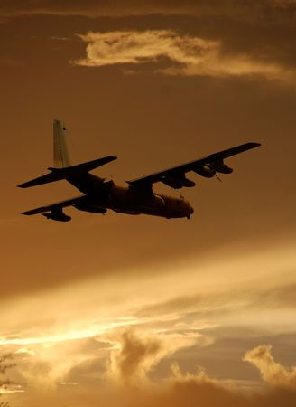 Military cargo jet flying at dawn
