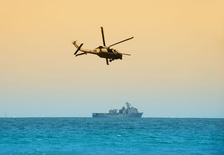 escorting: Military helicopter escorting navy cutter to mission Stock Photo