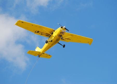 samll: Samll yellow airplane with banner towing rope Stock Photo