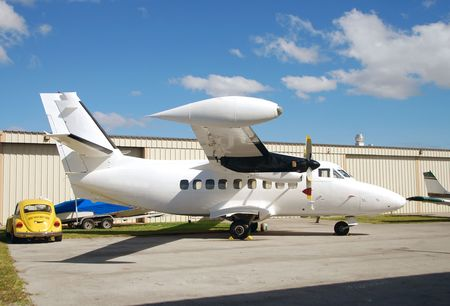 White airplane in front of hangar