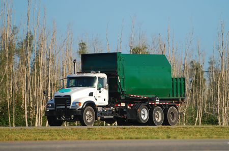 Green colored waste removal dump truck                                  photo