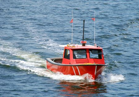 Red colored utility boat approaching