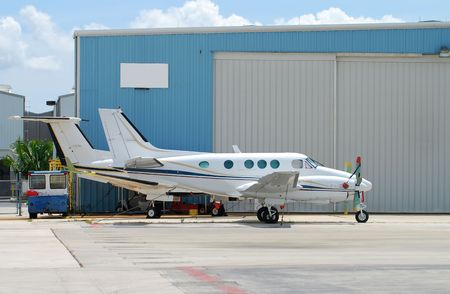 Two turboprop airplanes parked in front of hangar
