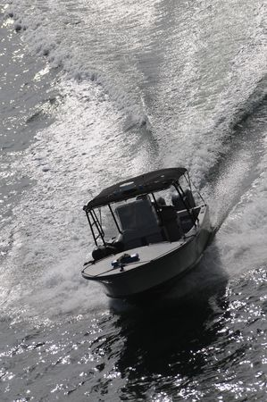 patrolling: Police motor boat patrolling harbor at high speed