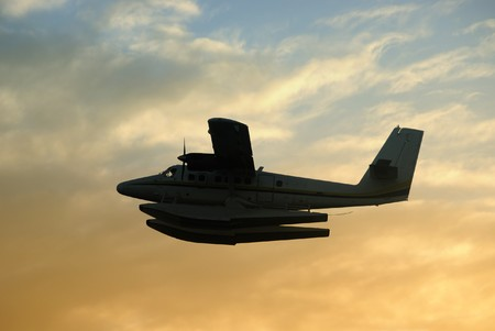 Flying boat airplane taking off at sunset