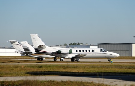 Three private charter jets parked on a tarmac