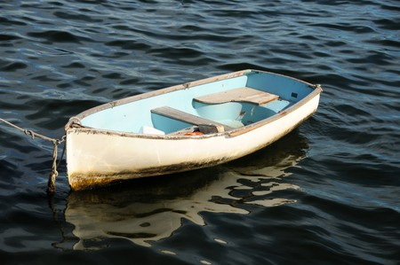 run down: Run down old boat floating in a bay Stock Photo