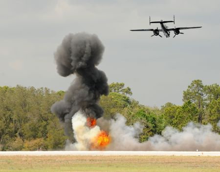 bombardment: Old bomber dropping bombs on a field Stock Photo