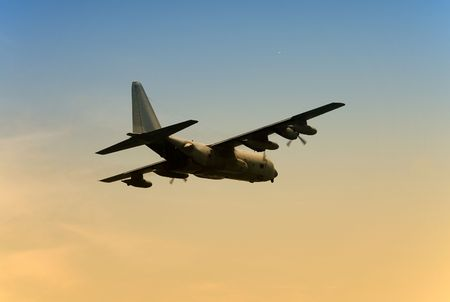 departing: Army transport airplane departing at dawn Stock Photo