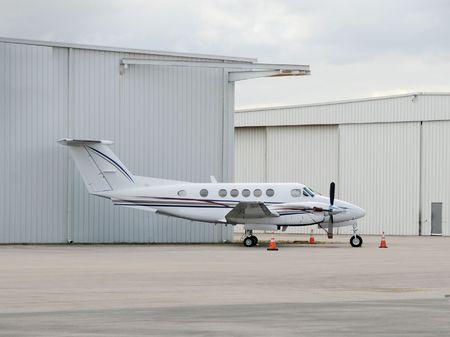 turboprop: Modern turboprop airplane parked near hangar