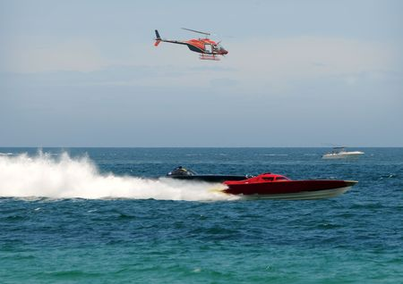 speedboats: Speed boards racing in the ocean and chased by helicopter Stock Photo